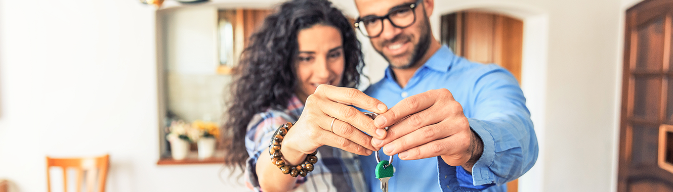 Couple holding new house keys.