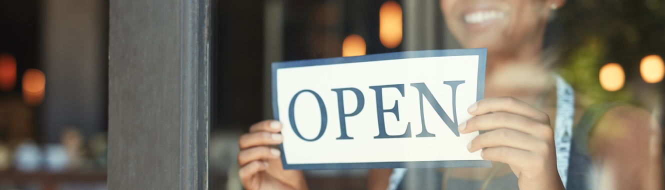 "A small business owner with an ""open"" sign"